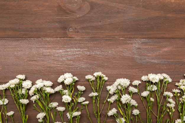 Pequeñas flores blancas sobre fondo de madera. Foto gratis