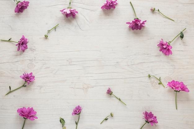 Pequeñas flores rosas esparcidas sobre mesa. Foto gratis