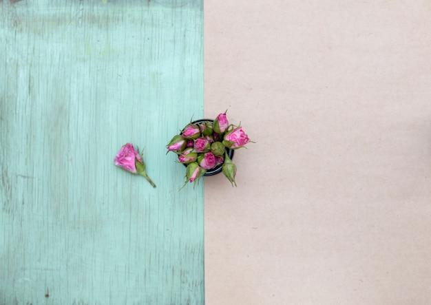 Pequeñas rosas rosadas en la superficie de madera y papel artesanal Foto Premium