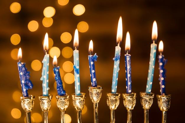 Pequeñas velas de menorá cerca de luces abstractas. Foto gratis