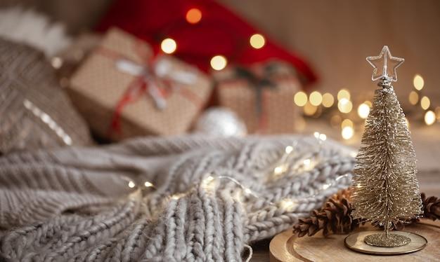 Pequeño árbol de navidad brillante decorativo en primer plano sobre un fondo borroso de una bufanda tejida, adornos navideños y luces bokeh copie el espacio. Foto gratis
