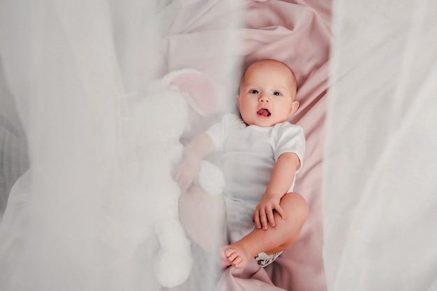Un pequeño bebé se acuesta en la cama con un conejo de juguete y sonríe. Foto Premium