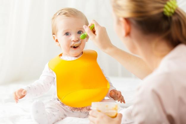 Pequeño bebé alimentándose con una cuchara Foto Premium