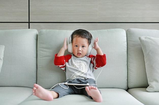 Pequeño bebé asiático lindo en auriculares está usando un teléfono inteligente Foto Premium