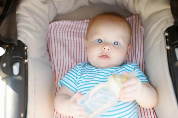 Pequeño bebé en cochecito con una botella de agua en el día de verano Foto Premium