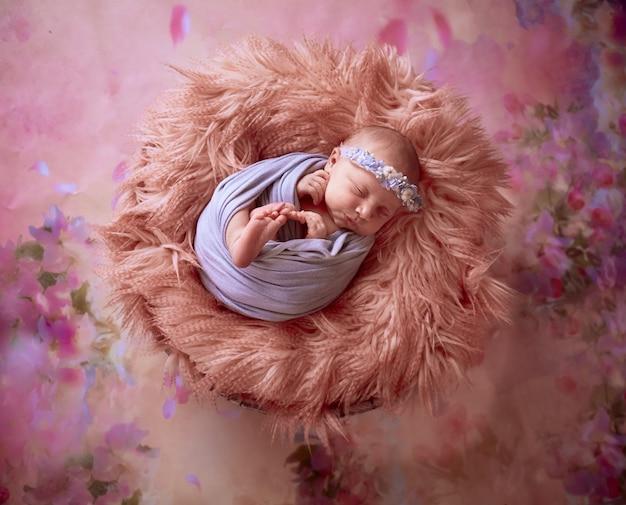 El pequeño bebé se encuentra en la canasta con cuadros Foto gratis