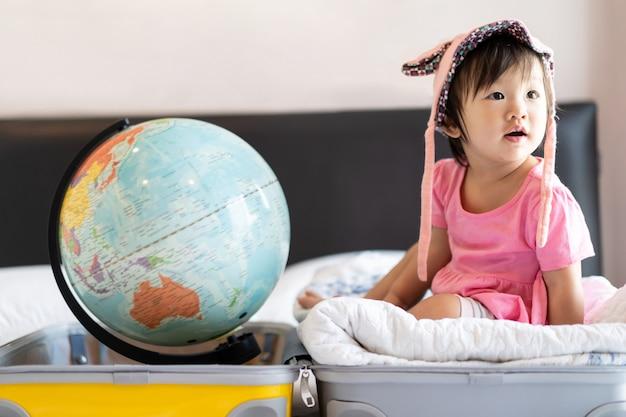 Pequeño bebé lindo asiático que lleva el sombrero que se sienta en bolso del viaje con la sonrisa que siente divertida y que ríe en cama en dormitorio. Foto Premium