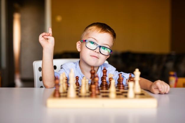Pequeño bebé con síndrome de down con grandes gafas azules jugando al ajedrez en el jardín de infantes Foto Premium