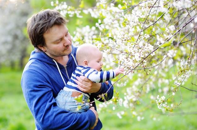 Pequeño bebé con su padre de mediana edad en el jardín de flores. Foto Premium