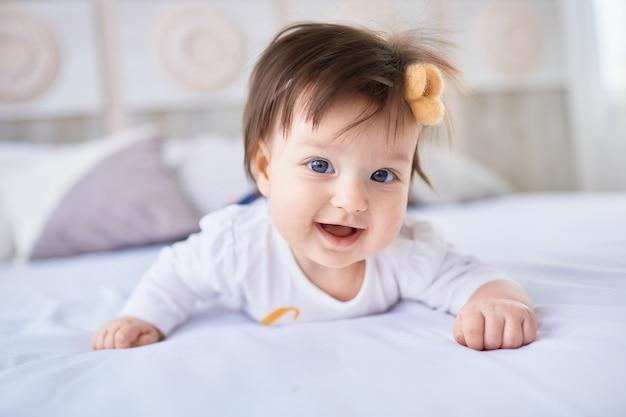 El pequeño bebé yace en la cama Foto gratis