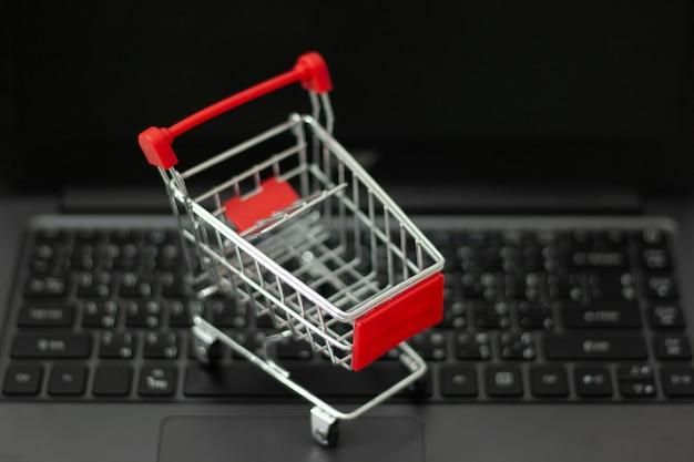 Pequeño carrito de compras en la computadora portátil para compras en línea. concepto de compras en línea Foto Premium