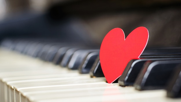 Pequeño corazón de papel rojo en teclas de piano Foto Premium