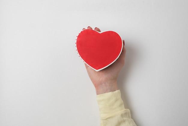 Pequeño cuadro rojo en forma de corazón en la palma femenina aislado en Foto Premium