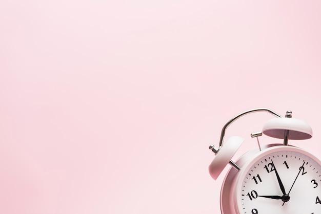 Pequeño despertador en la esquina del fondo rosa. Foto gratis