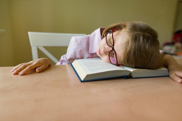 Pequeño estudiante con gafas duerme en un escritorio Foto Premium