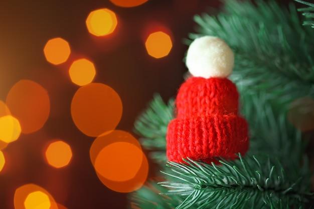 Pequeño gorro de punto en el árbol de navidad Foto Premium