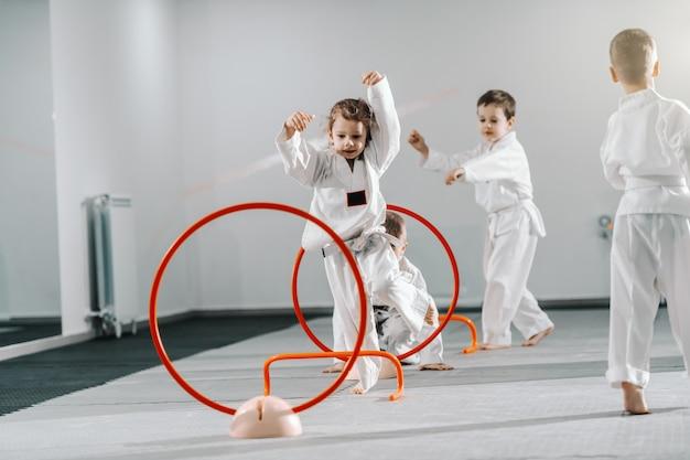 Pequeño grupo de niños caucásicos en doboks practicando taekwondo y calentando para treining mientras están descalzos. Foto Premium