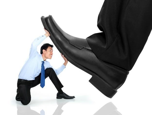 Pequeño hombre de negocios siendo aplastado por los pies Foto Premium