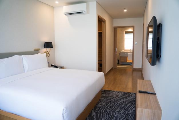 Pequeño interior de habitación de hotel con cama doble y baño. Foto gratis