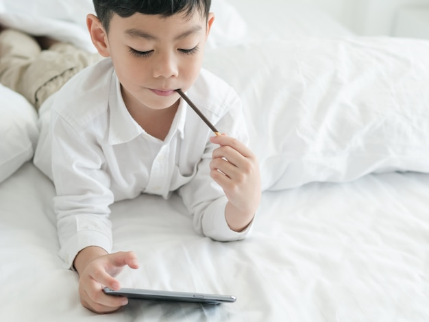 El pequeño niño asiático lindo se centró en smartphone mientras que miente en la cama Foto Premium