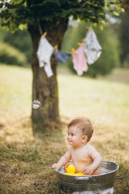 Pequeño niño bañándose en el parque Foto gratis