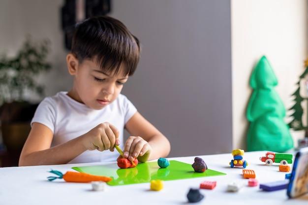 Pequeño niño caucásico jugando con plastilina de colores y haciendo figuras sobre la mesa blanca. idea de niño feliz Foto gratis