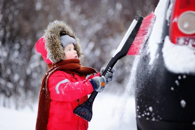 Pequeño niño lindo que ayuda a cepillar una nieve de un coche. niño pequeño usando una herramienta para limpiar el carro de los padres Foto Premium