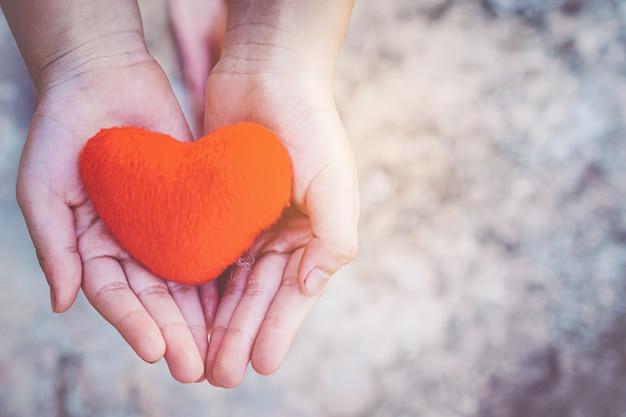 Pequeño niño manos sosteniendo el corazón Foto Premium