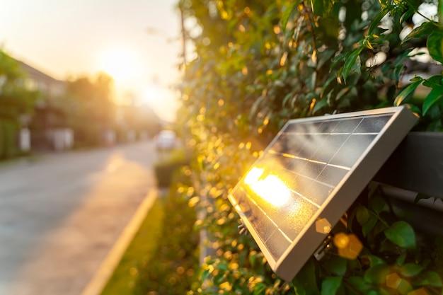 Pequeño panel solar en pared con luz solar. energía verde en el concepto de hogar. Foto Premium