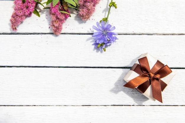 Pequeño regalo con vista superior de flores. Foto gratis