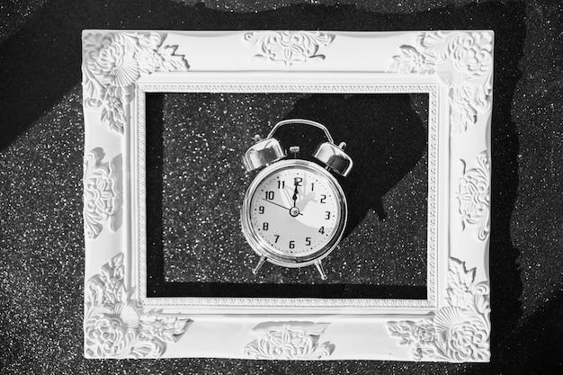 Pequeño reloj en marco sobre mesa Foto gratis