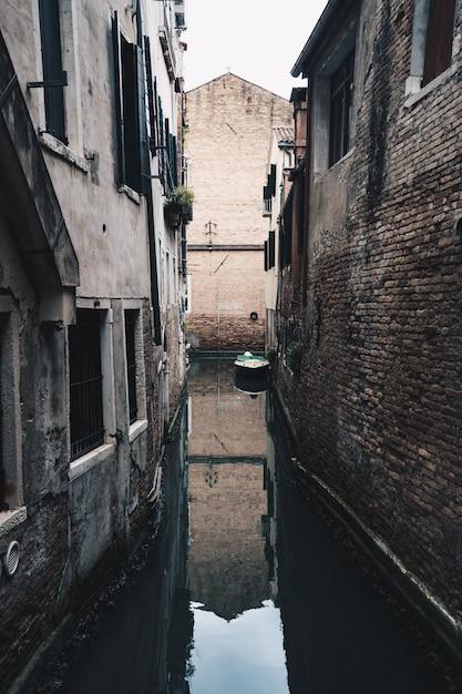 Pequeño río estrecho corriendo arrojar una ciudad suburbana entre edificios de ladrillo Foto gratis