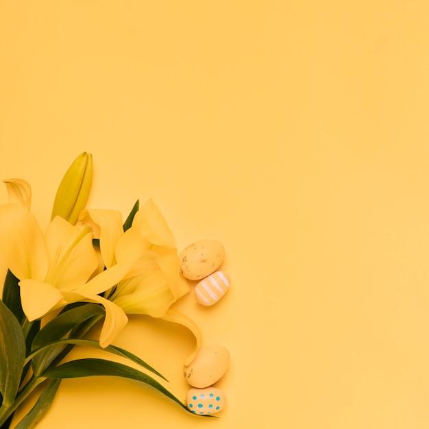 Pequeños huevos de pascua con hermosas flores de lirio amarillo sobre fondo amarillo Foto gratis