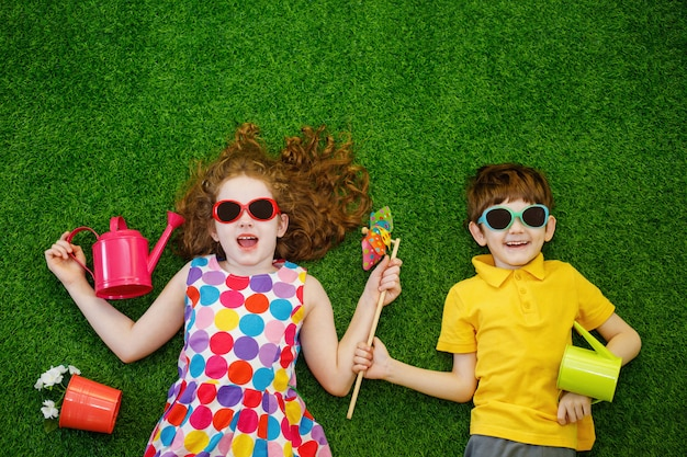 Pequeños jardineros de los niños que mienten en hierba verde. Foto Premium