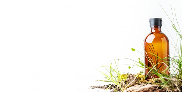 Pequeños musgos y hierba de productos cosméticos orgánicos en frasco de vidrio marrón Foto Premium