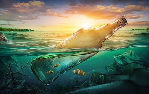 Pequeños peces en una botella entre la contaminación del océano. Foto Premium