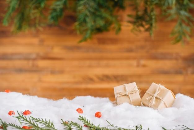 Pequeños regalos en la nieve con ramas de coníferas. Foto gratis