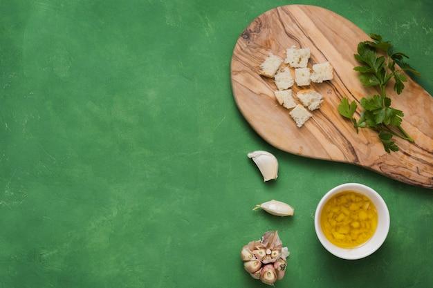 Pequeños trozos de pan; perejil; ajo y tazón de aceite de oliva infundido sobre fondo verde con textura Foto gratis