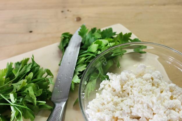 Perejil fresco con cuchillo sobre una tabla para cortar madera Foto Premium