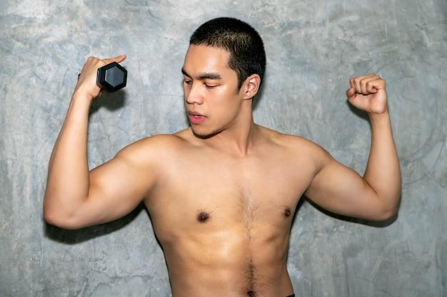 Perfecto culturista fuerte atlético hombre asiático entrenamiento brazo con mancuernas en el fondo. Foto Premium