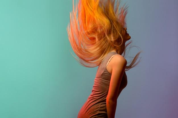 Perfil de bastante joven rubia sacudiendo su cabello Foto gratis