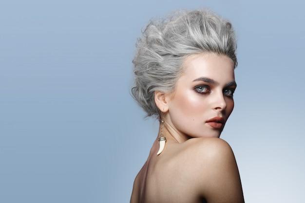 Perfil de hermosa joven modelo con peinado gris, hombros desnudos, maquillaje, ojos ahumados, aislado sobre fondo azul. Foto Premium
