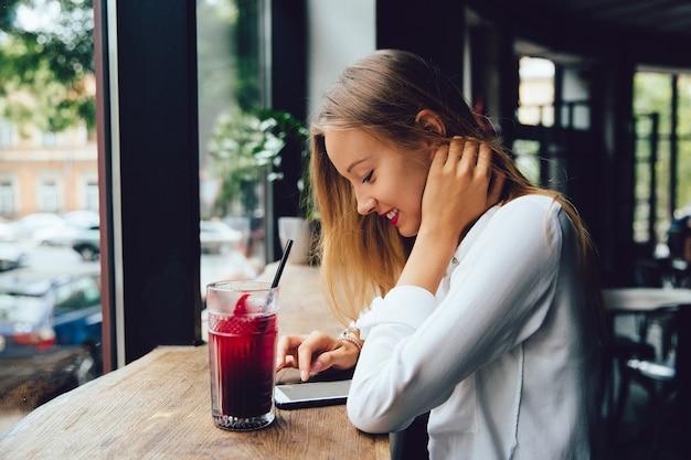 Perfil de mujer rubia joven sonriente, usando un teléfono inteligente, mensajes de texto un mensaje Foto gratis
