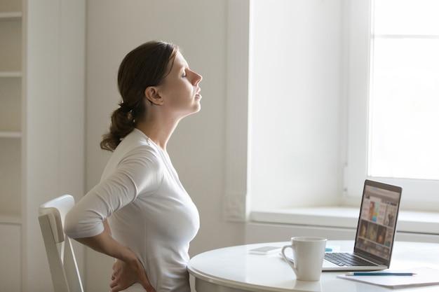 Perfil retrato de una mujer en el escritorio de estiramiento, positio de espalda Foto gratis