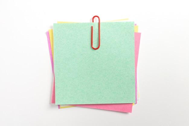 Perno de papel colorido de la nota con los clips de papel rojos y aislado en blanco. Foto gratis
