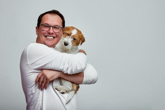 El perro se acuesta sobre el hombro de su dueño. jack russell terrier en las manos de su dueño en el fondo blanco. el concepto de personas y animales. t Foto Premium