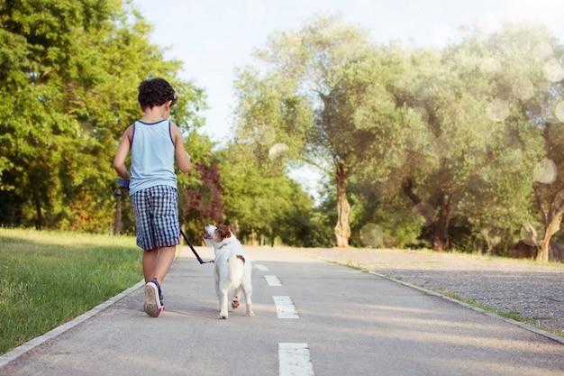 Perro y niño hacia atrás caminando en la puesta del sol del parque. Foto Premium