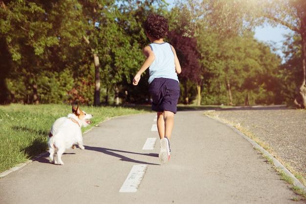 Perro y niño corriendo en el parque. sin correa. concepto de amistad Foto Premium