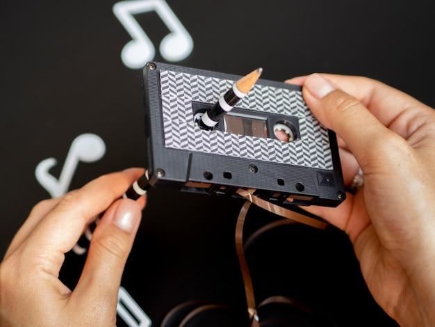 Persona arreglando cinta de cassette con patrón moderno Foto gratis
