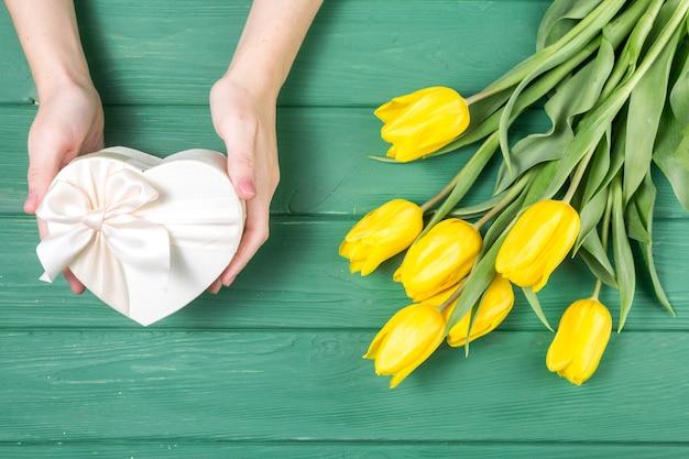 Persona con caja de regalo en forma de corazón cerca de tulipanes Foto gratis